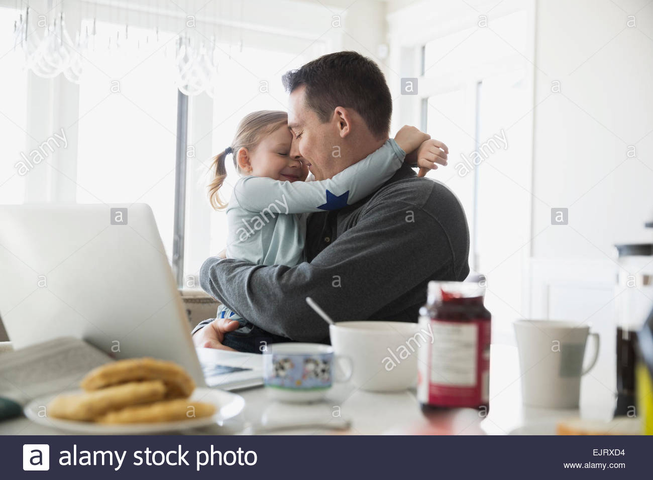 Affectionate father and daughter hugging tenderly in kitchen Stock Photo