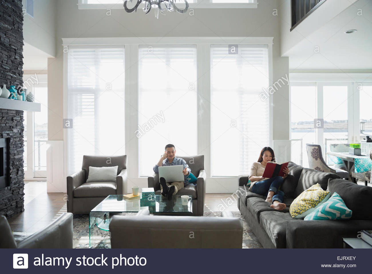 Couple relaxing book and laptop in living room Stock Photo: 80430979 ...
