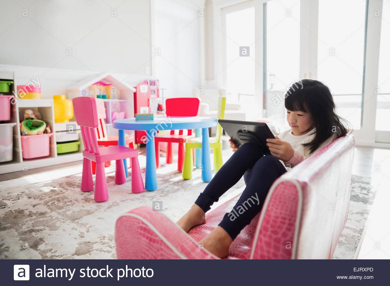 Girl using digital tablet on sofa in playroom Stock Photo