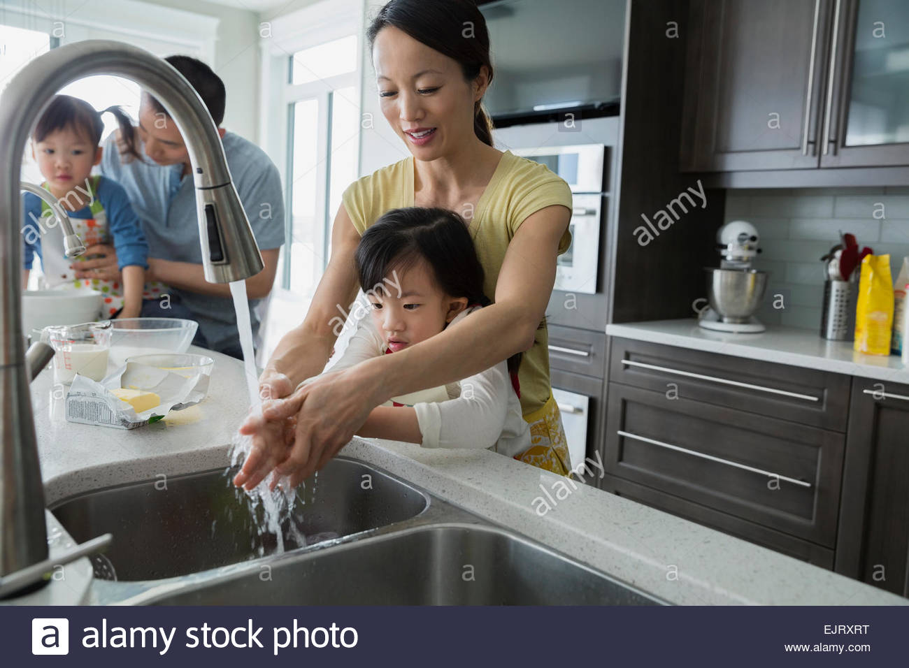 Mother and daughter washing hands in kitchen sink - Stock Image