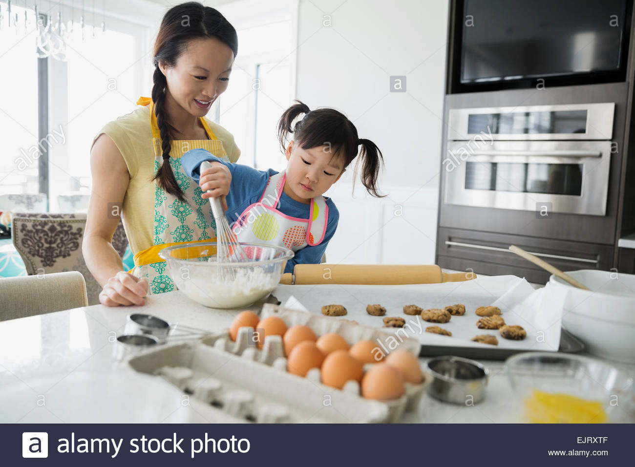 Mother and daughter baking cookies in kitchen - Stock Image