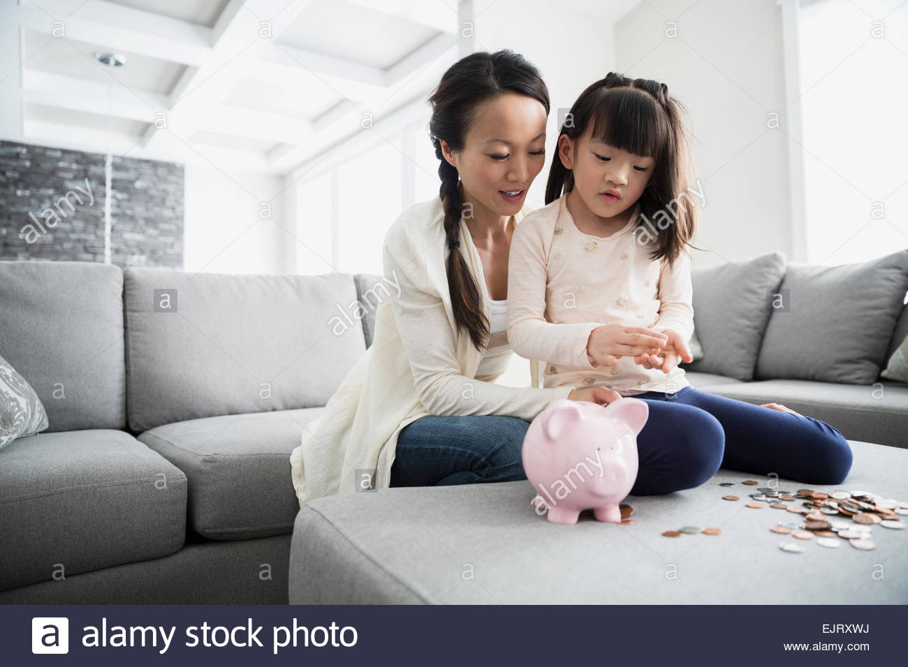 Mother and daughter counting coins from piggy bank - Stock Image