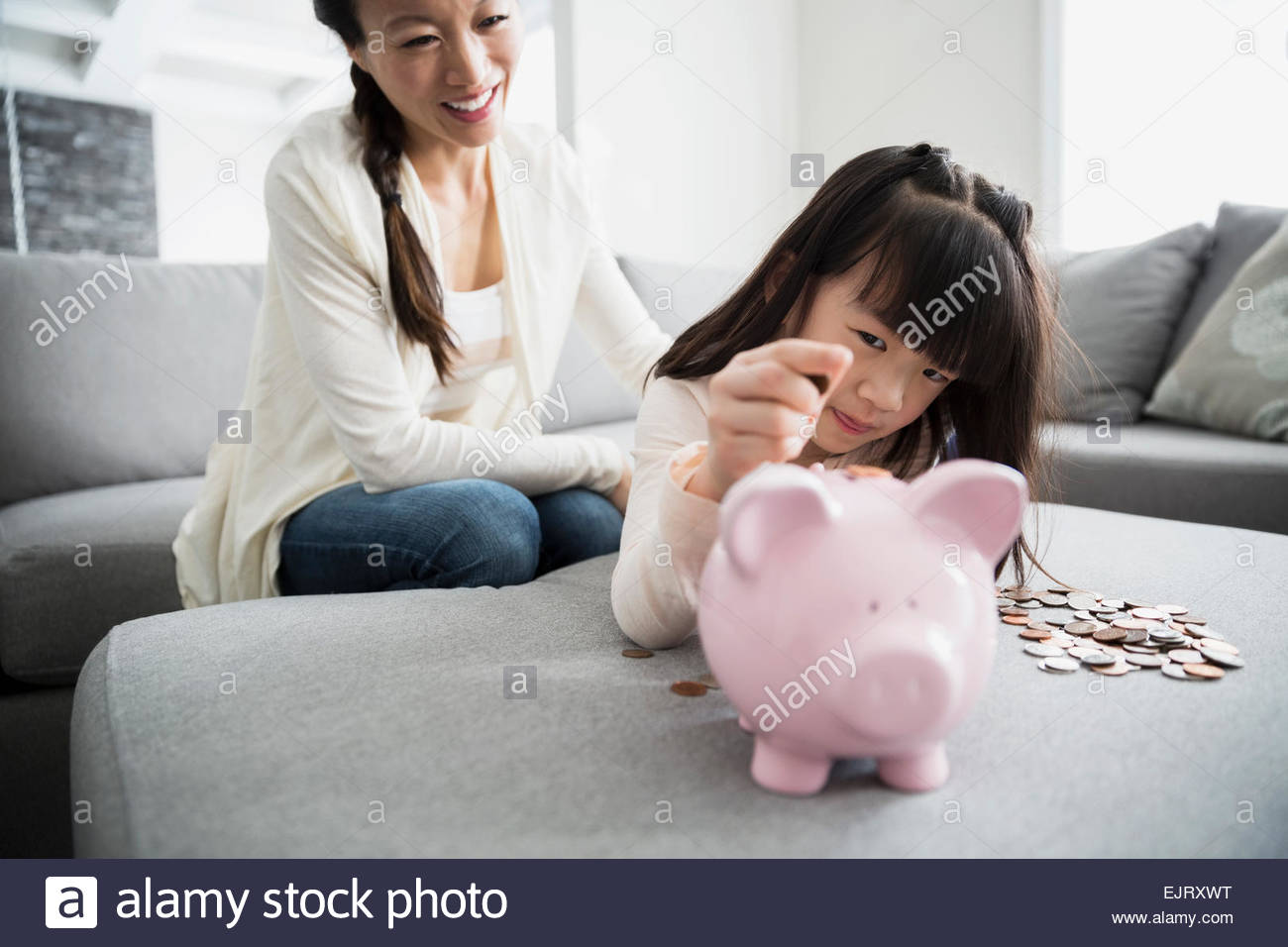 Mother watching daughter deposit coin into piggy bank - Stock Image