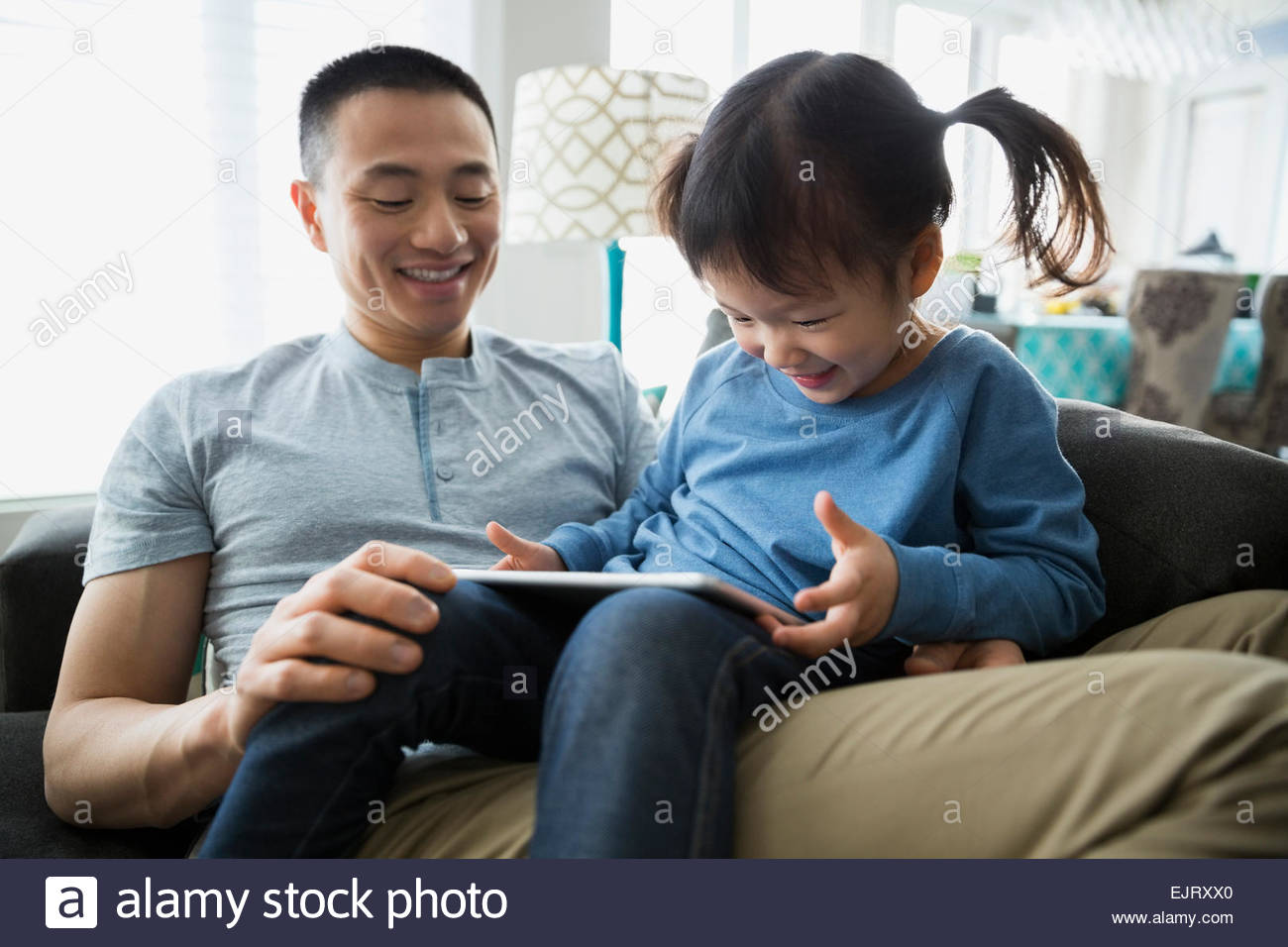 Father and daughter using digital tablet - Stock Image