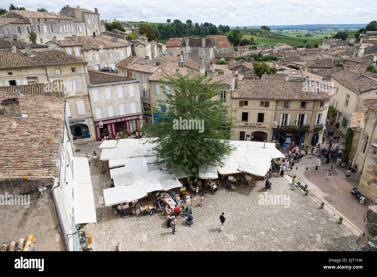 View from the church tower in St Emilion of the cafe and square below together with the tiled rooftops and countryside - Stock Image