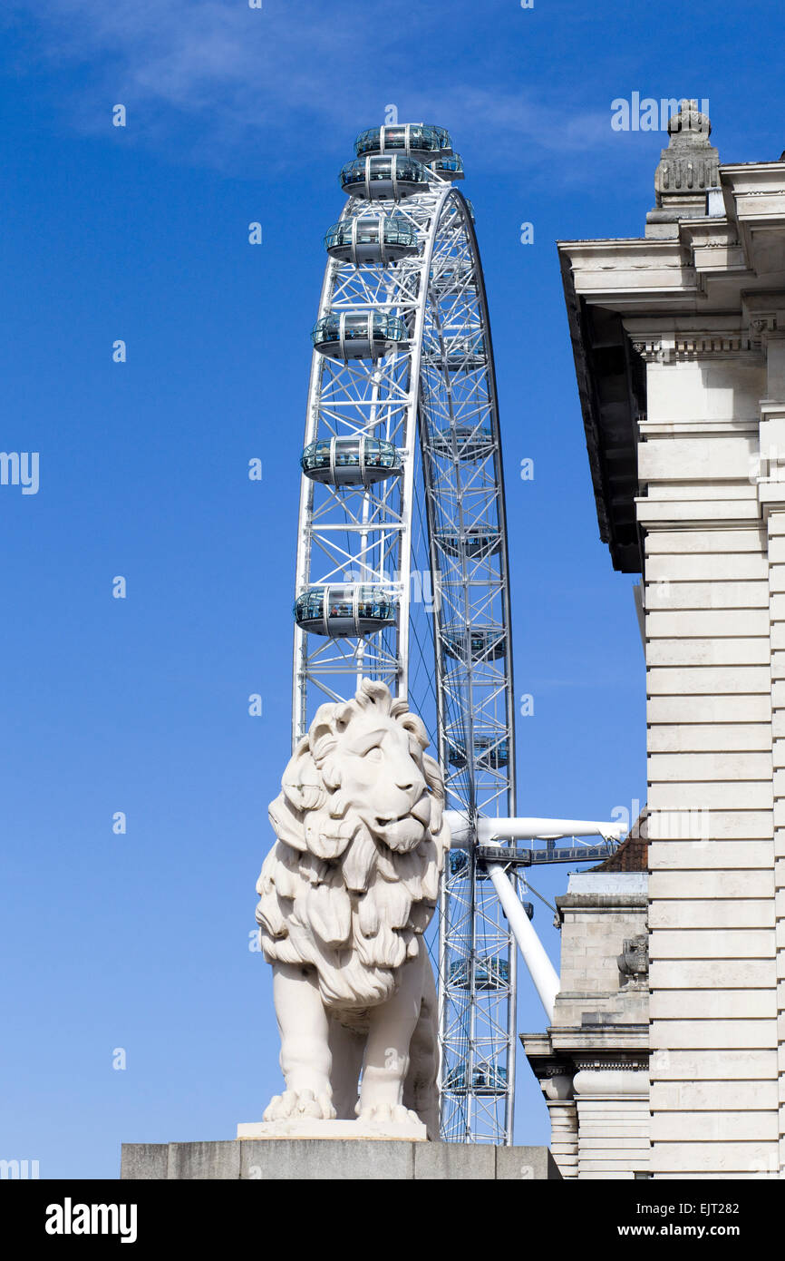 The Coade stone lion guarding the southern end of the Westminster bridge with London Eye in the background England - Stock Image