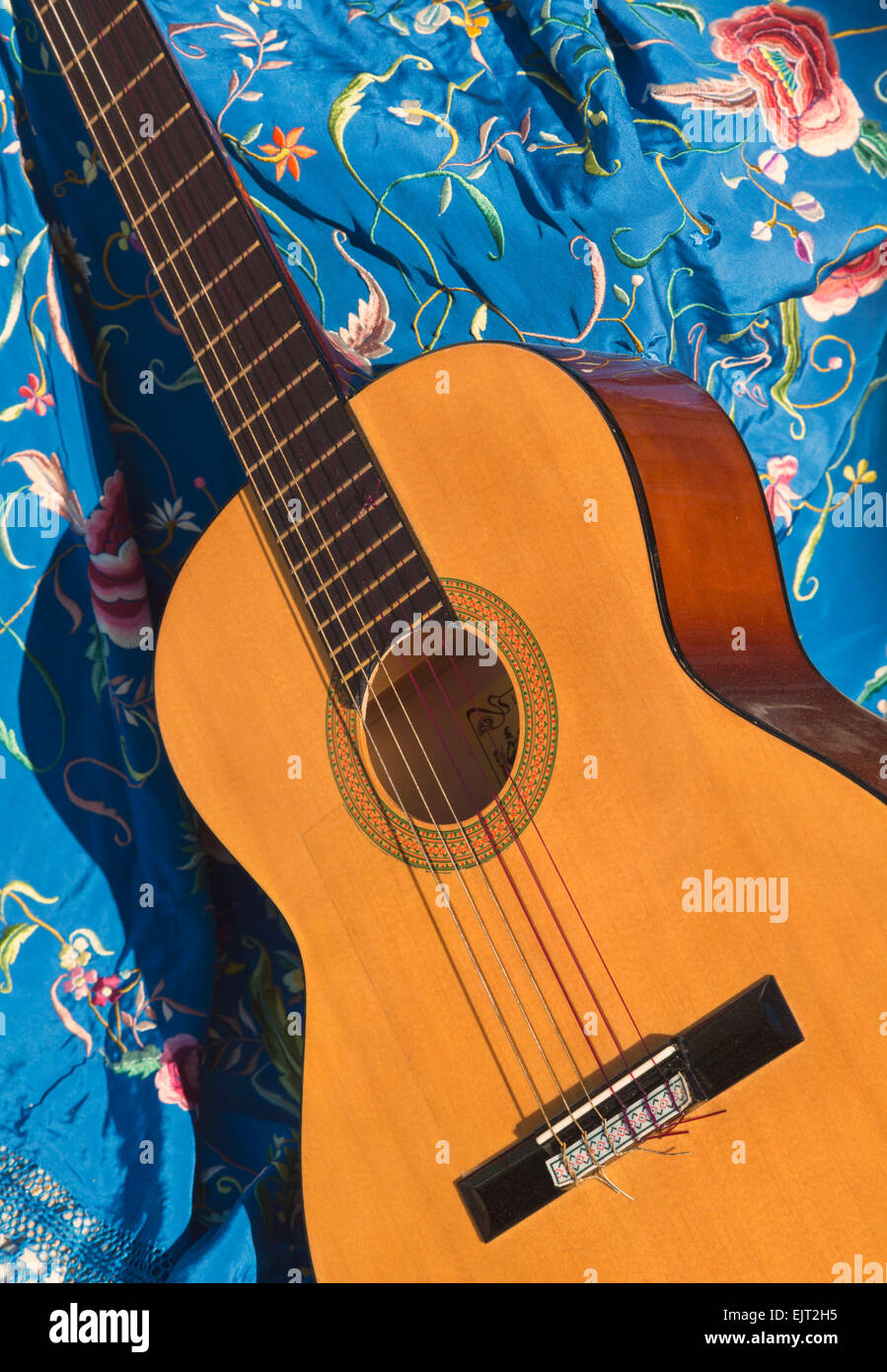 Spanish guitar resting on a shawl. - Stock Image
