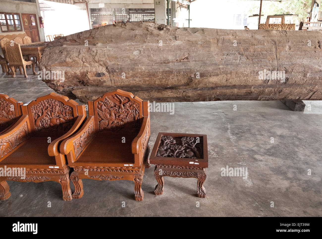 Chiang Mai, Northern Thailand, hardwood carving, chairs, teak log in background - Stock Image