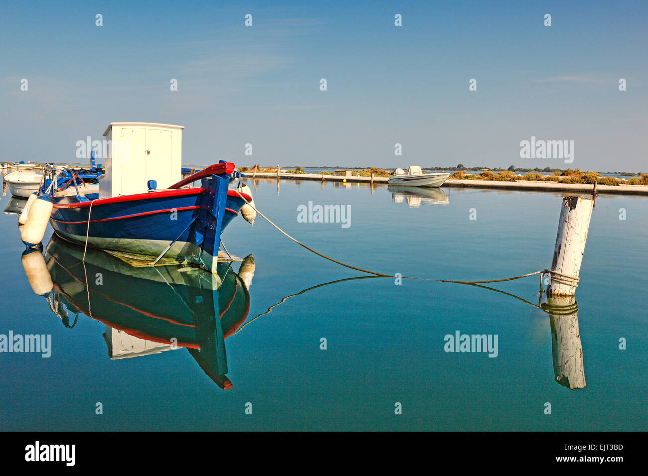 A fishing boat tied up in shallow waters in the city of Lefkada, Greece - Stock Image