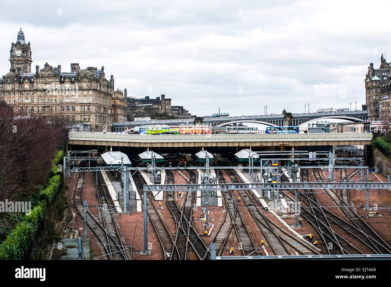 A view of the cluster of train lines running under the bridges and into the train station in Edinburgh, Scotland. - Stock Image