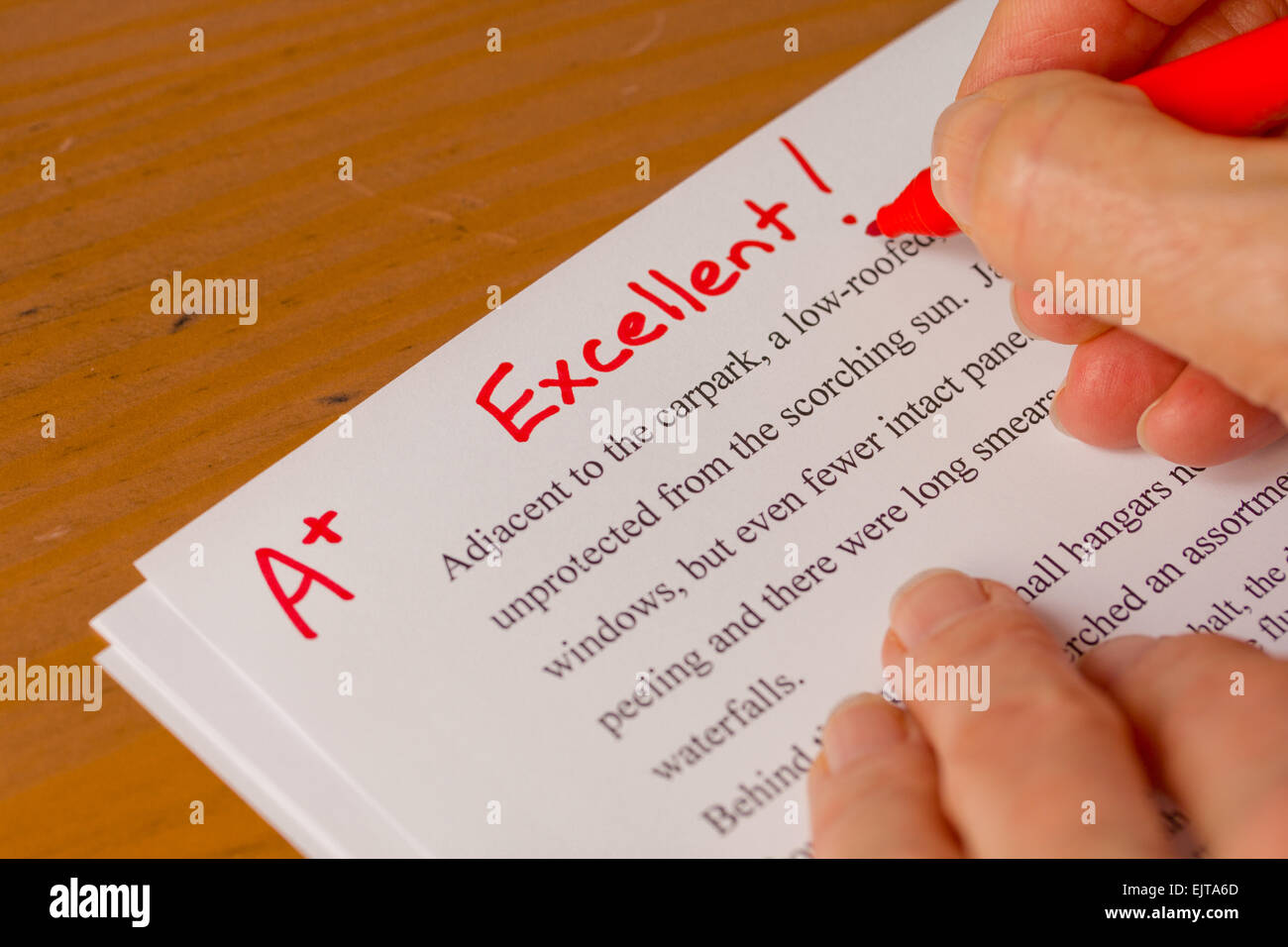 Hand with Red Pen Grading Papers with Excellent - Success concept in education industry - Stock Image