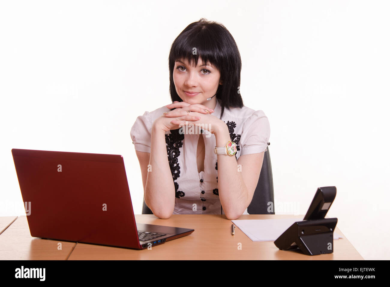Pretty girl sitting in a call center with a laptop in a white blouse with black embroidery - Stock Image
