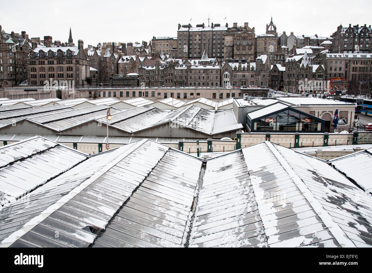 View towards Edinburgh's Old Town with the snow covered rooftop of Waverley Station in the foreground. - Stock Image