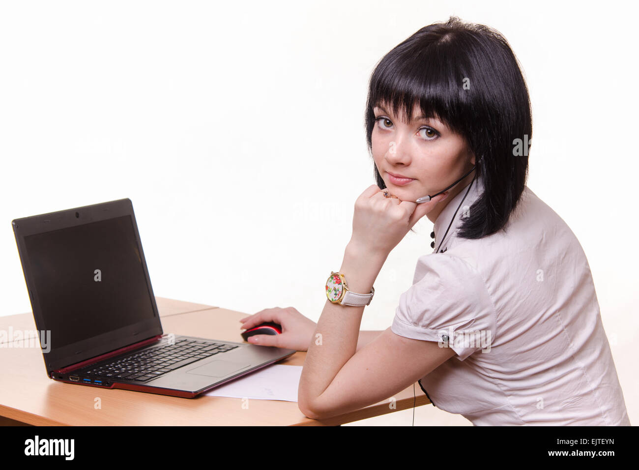 Cute office girl sitting at a table with a laptop in white blouse - Stock Image