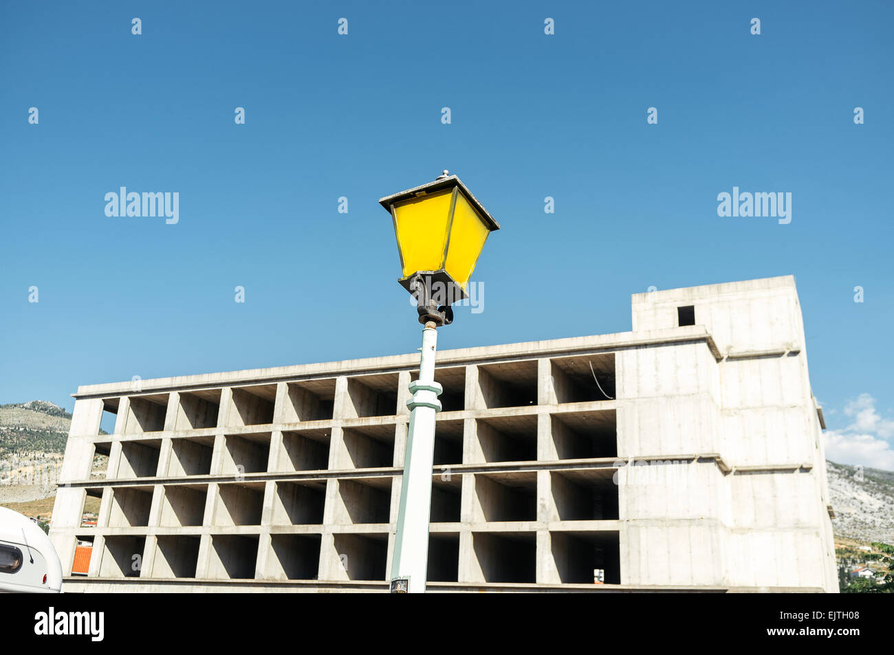 Low angle view of street light against incomplete building - Stock Image