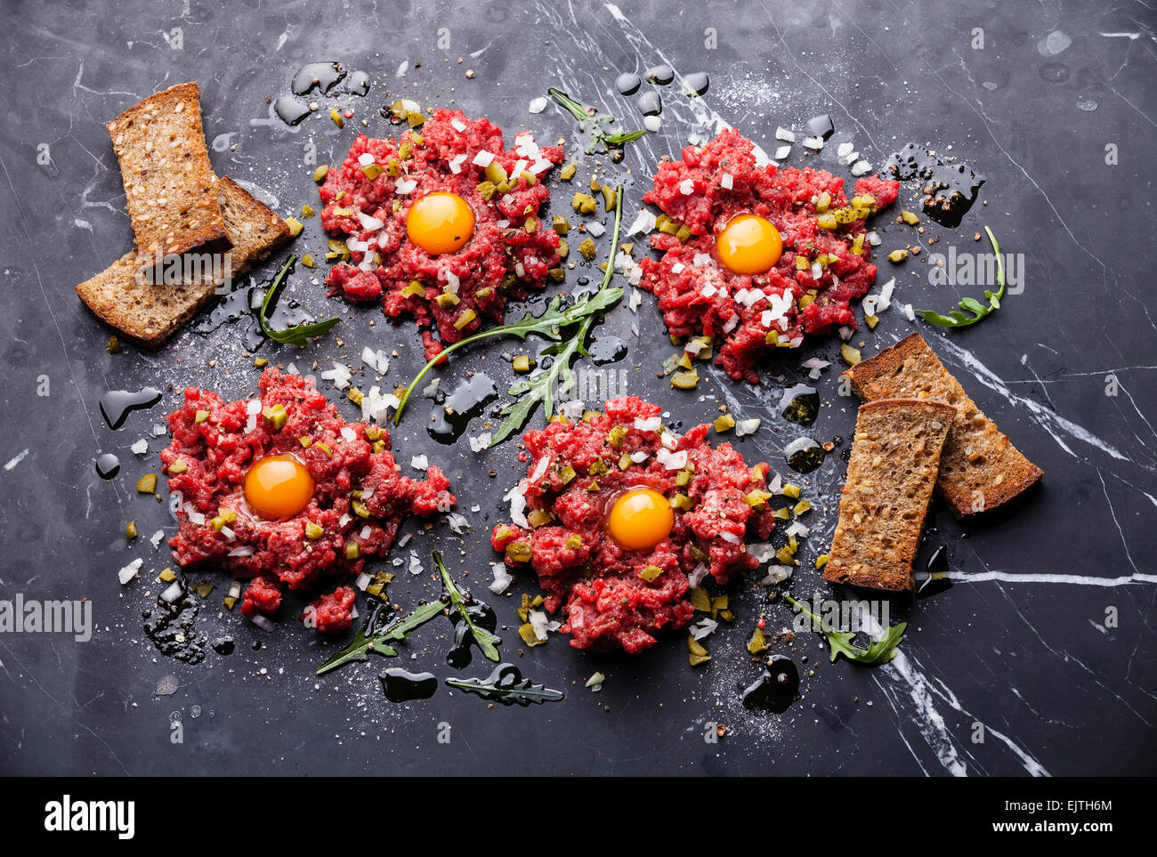 Beef tartare with pickled cucumber and fresh onion on dark marble background - Stock Image