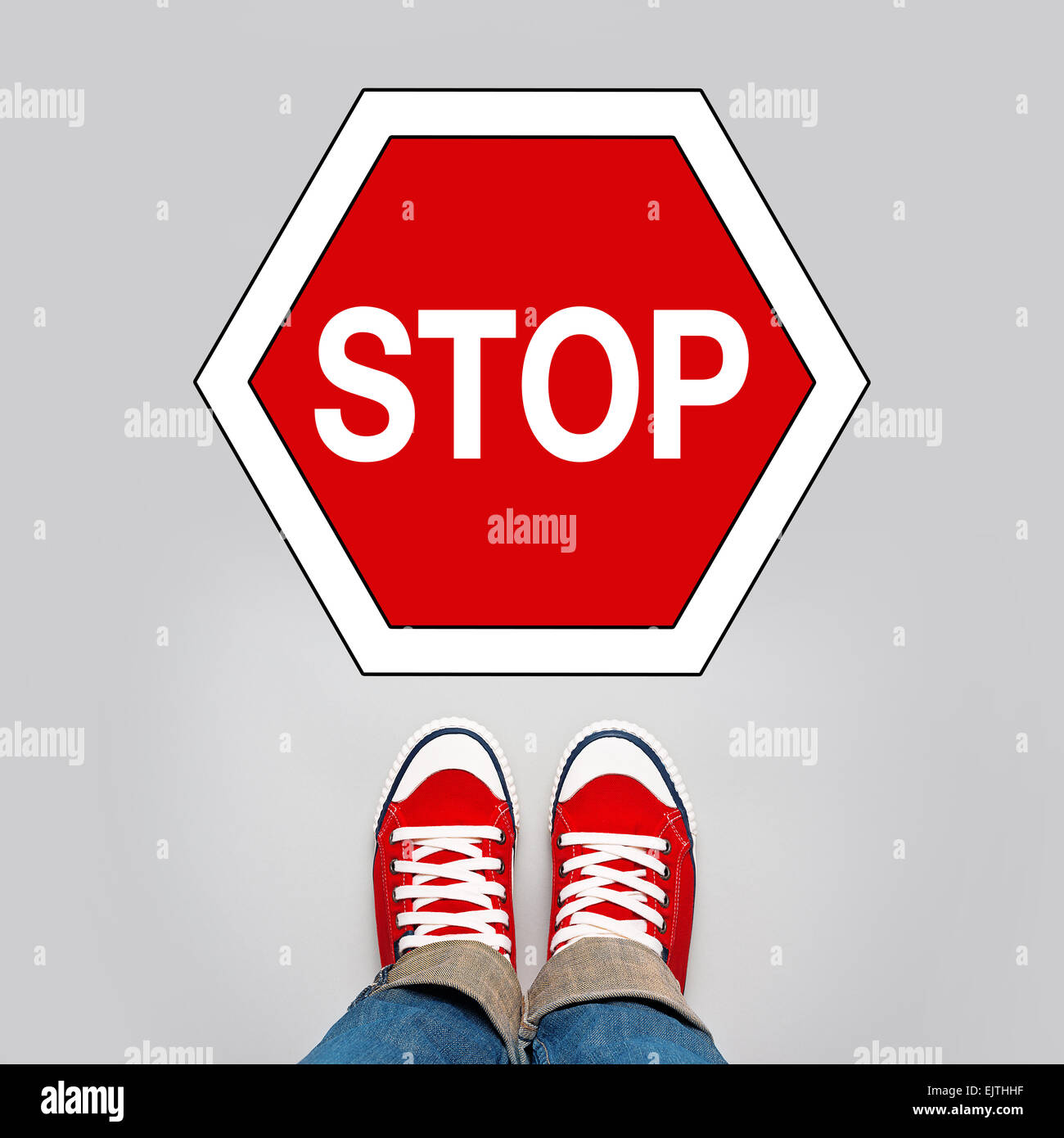 Stop Concept, Young Teenage Person in Red Sneakers Standing in Front of Stop Traffic Sign Stock Photo
