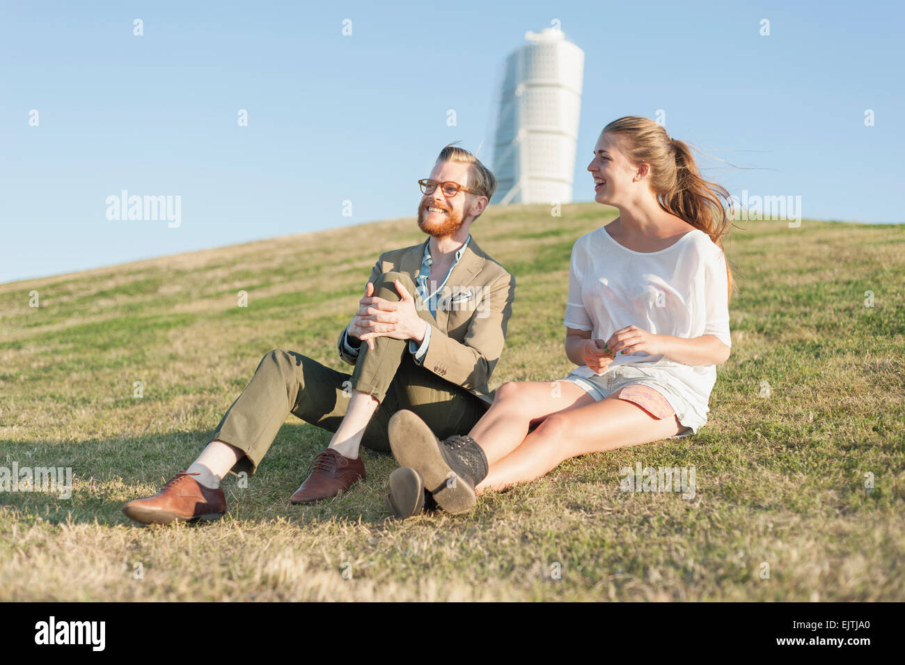 Happy couple sitting on grassy hill in city Stock Photo