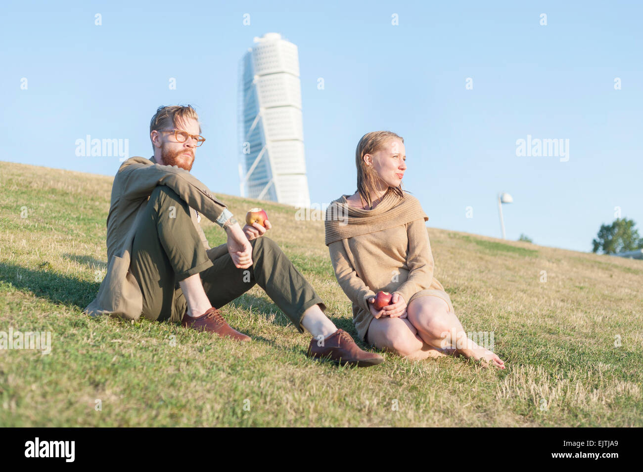 Low angle view of couple eating apples on grassy hill against Turing Torso - Stock Image