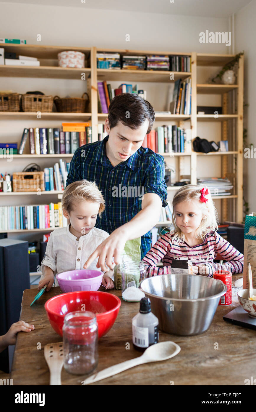Young man guiding children in baking at home - Stock Image