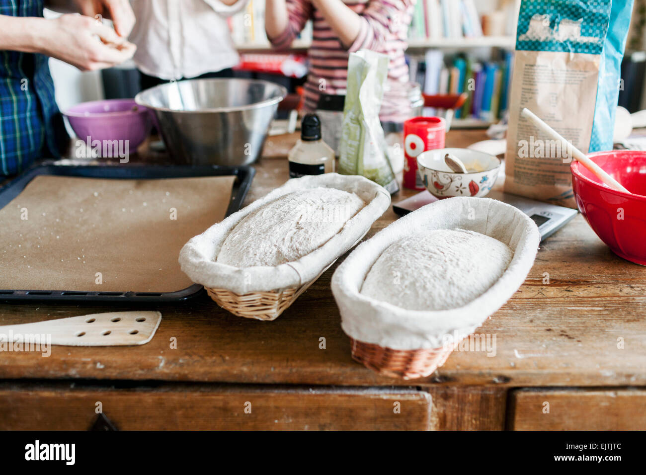 Close-up of dough in baskets with family in background - Stock Image