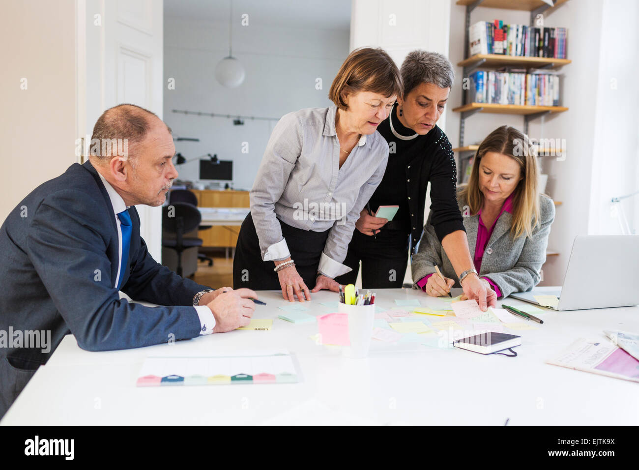 Businesswomen communicating over reminder notes at office desk - Stock Image