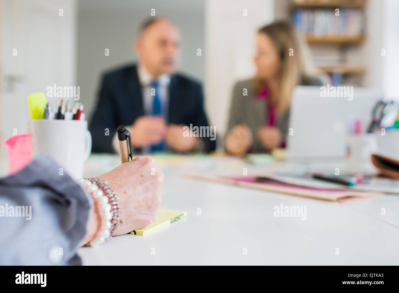 Cropped image of hand writing reminder in front of colleagues at office desk - Stock Image