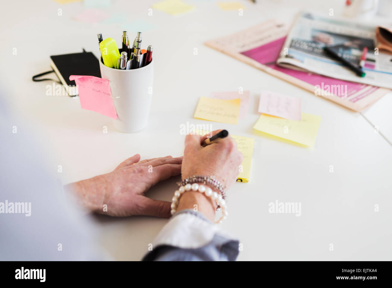 Cropped image of businesswoman writing reminder at office desk - Stock Image