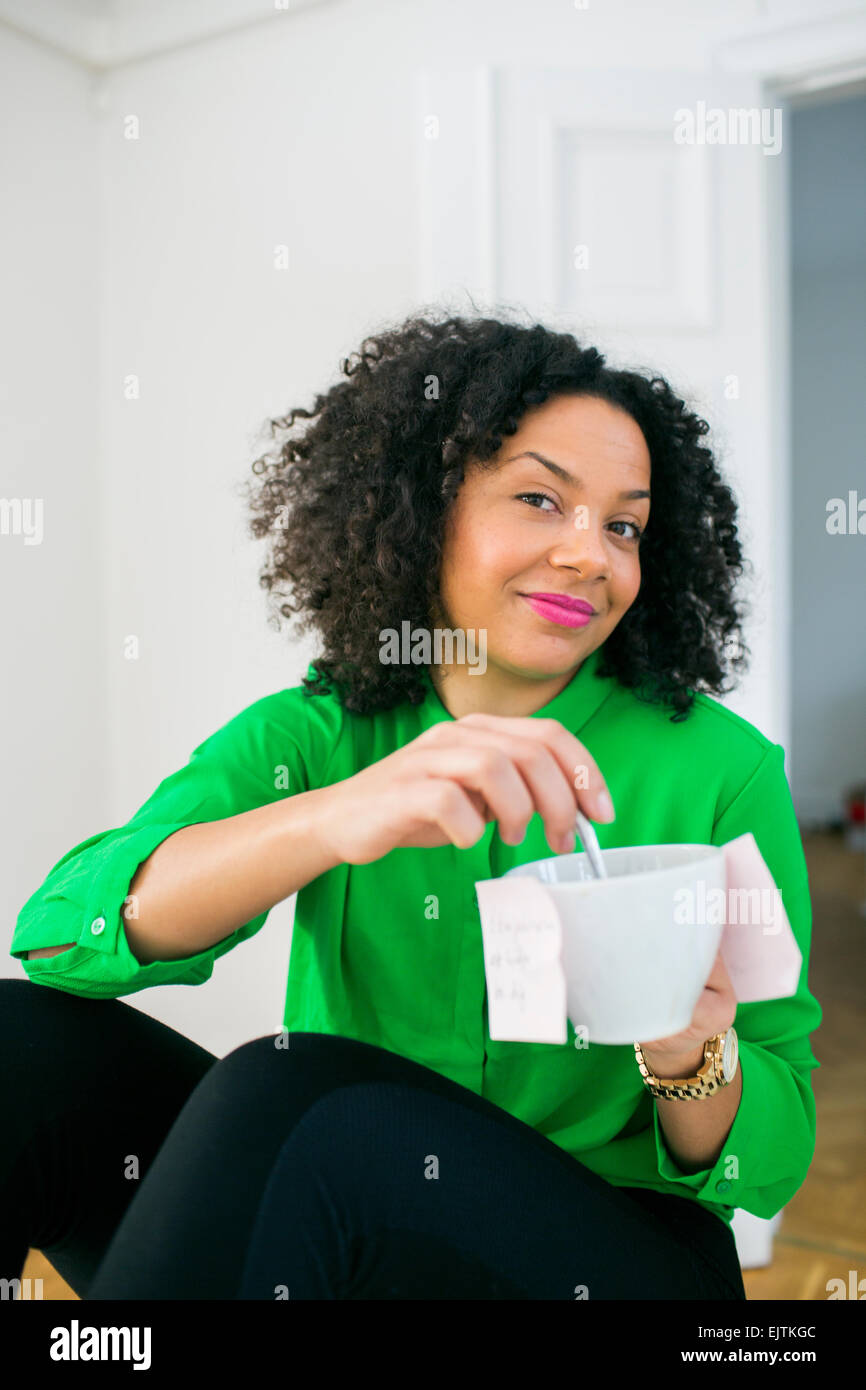 Portrait of young businesswoman with adhesive notes stuck on coffee cup in office - Stock Image