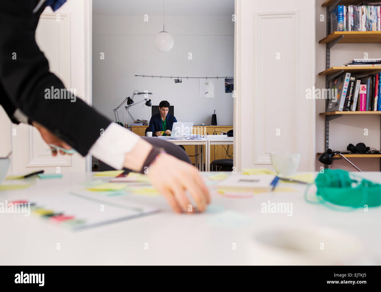 Cropped image of businessman's hand holding reminder notes while colleague working in background - Stock Image