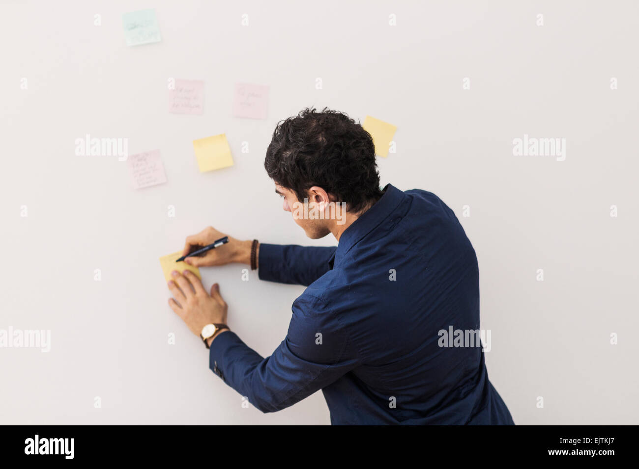 Rear view of young businessman writing reminders on adhesive note stuck on whiteboard - Stock Image