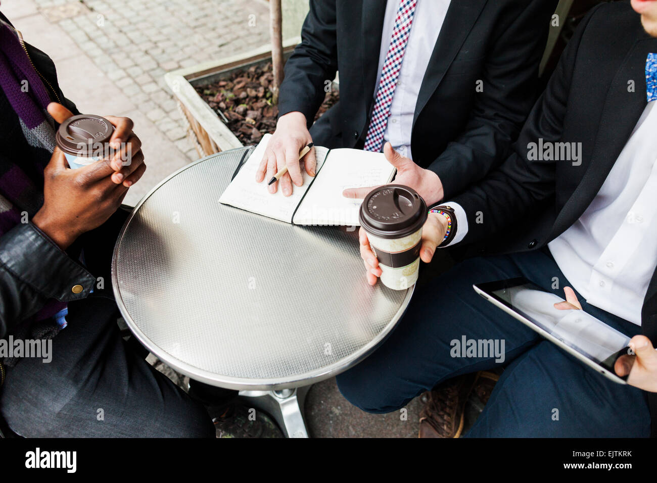 Business people with diary and disposable cups at sidewalk cafe - Stock Image