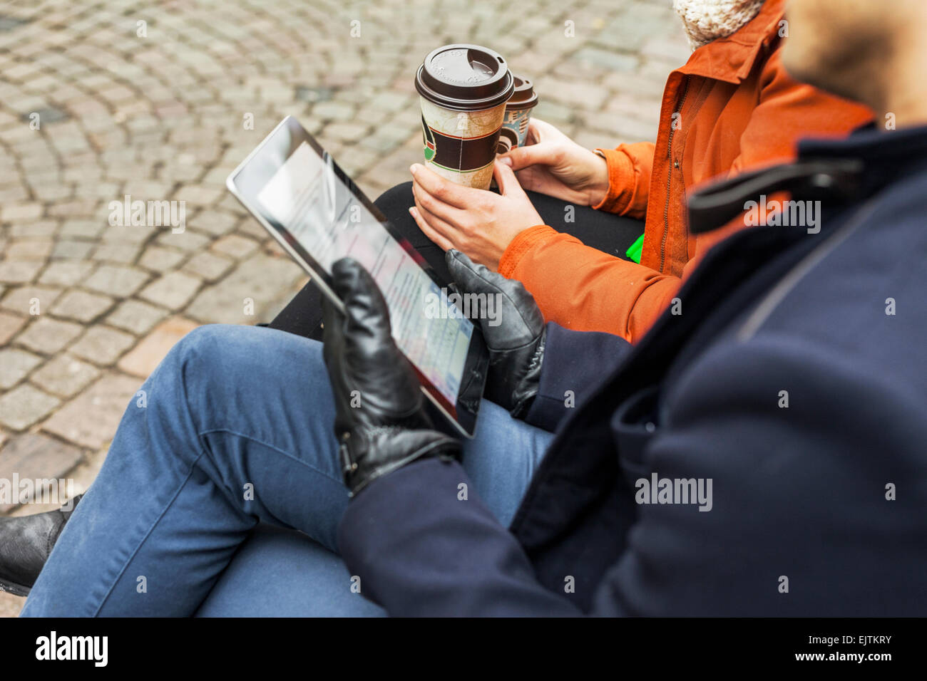 Midsection of man and woman with digital tablet and disposable coffee cups on sidewalk - Stock Image
