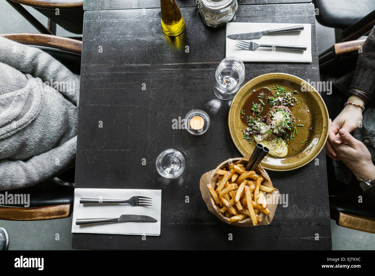 Cropped image of mother and son with food served on table - Stock Image