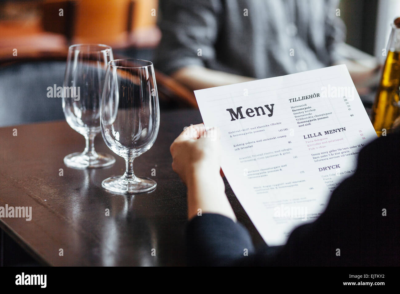 Cropped image of woman holding menu while sitting with man in restaurant - Stock Image