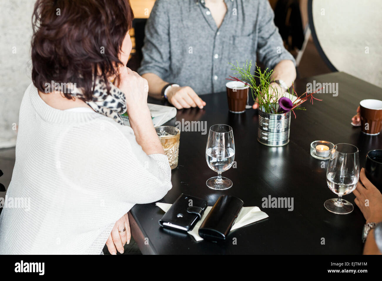 Mature woman with friends sitting at table in restaurant - Stock Image