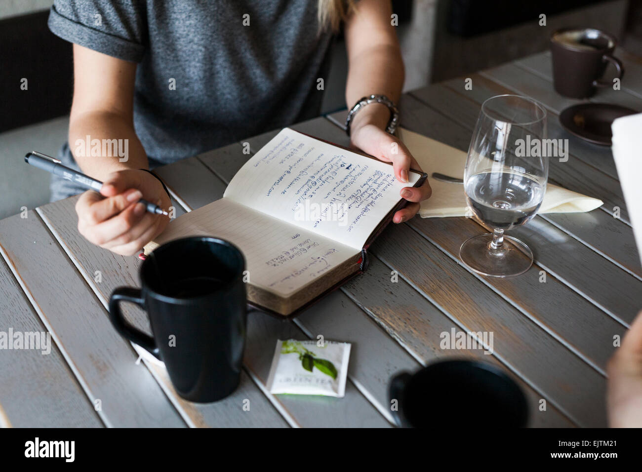 Midsection of woman writing in book - Stock Image
