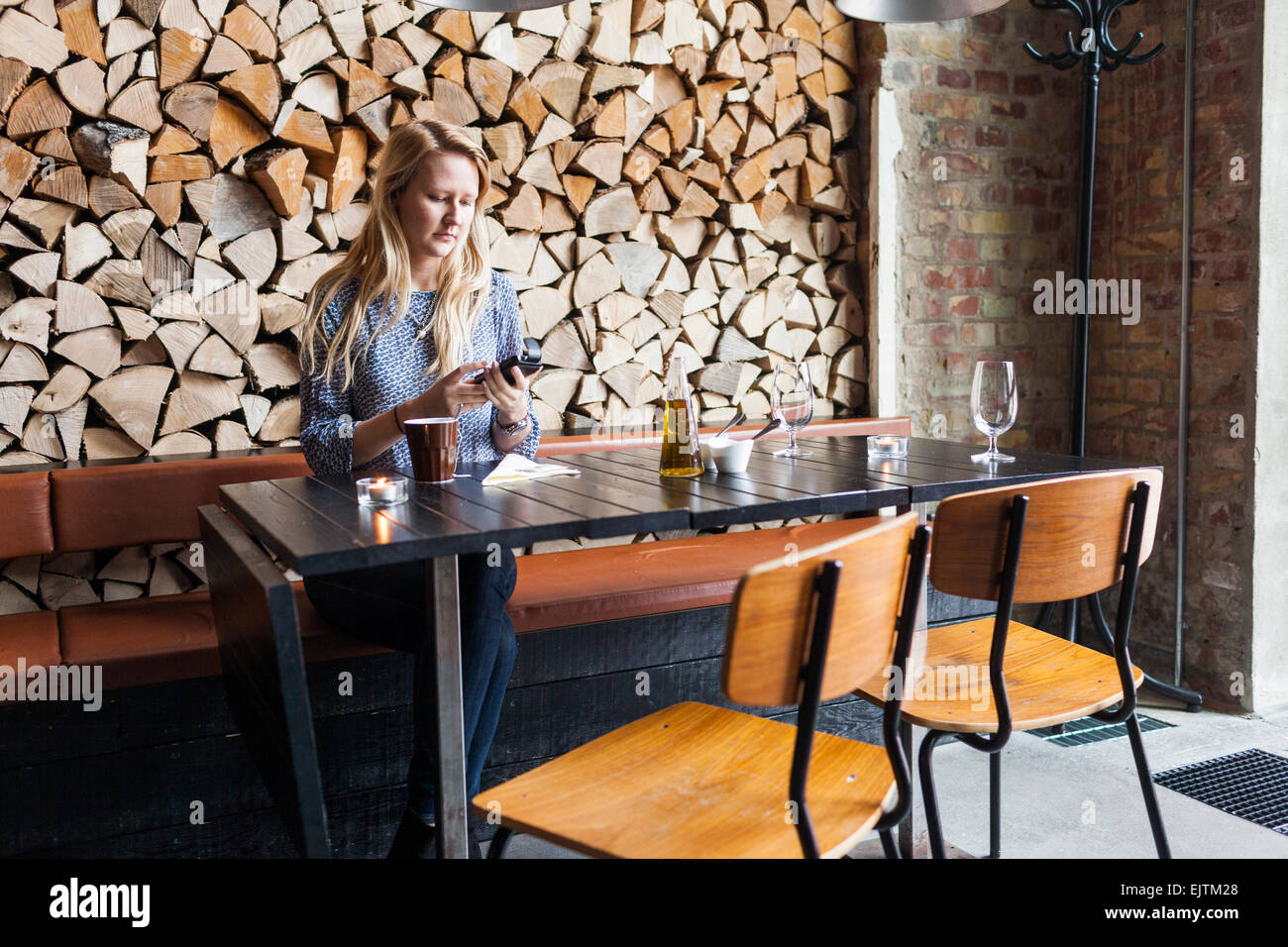 Young woman using mobile phone in restaurant - Stock Image