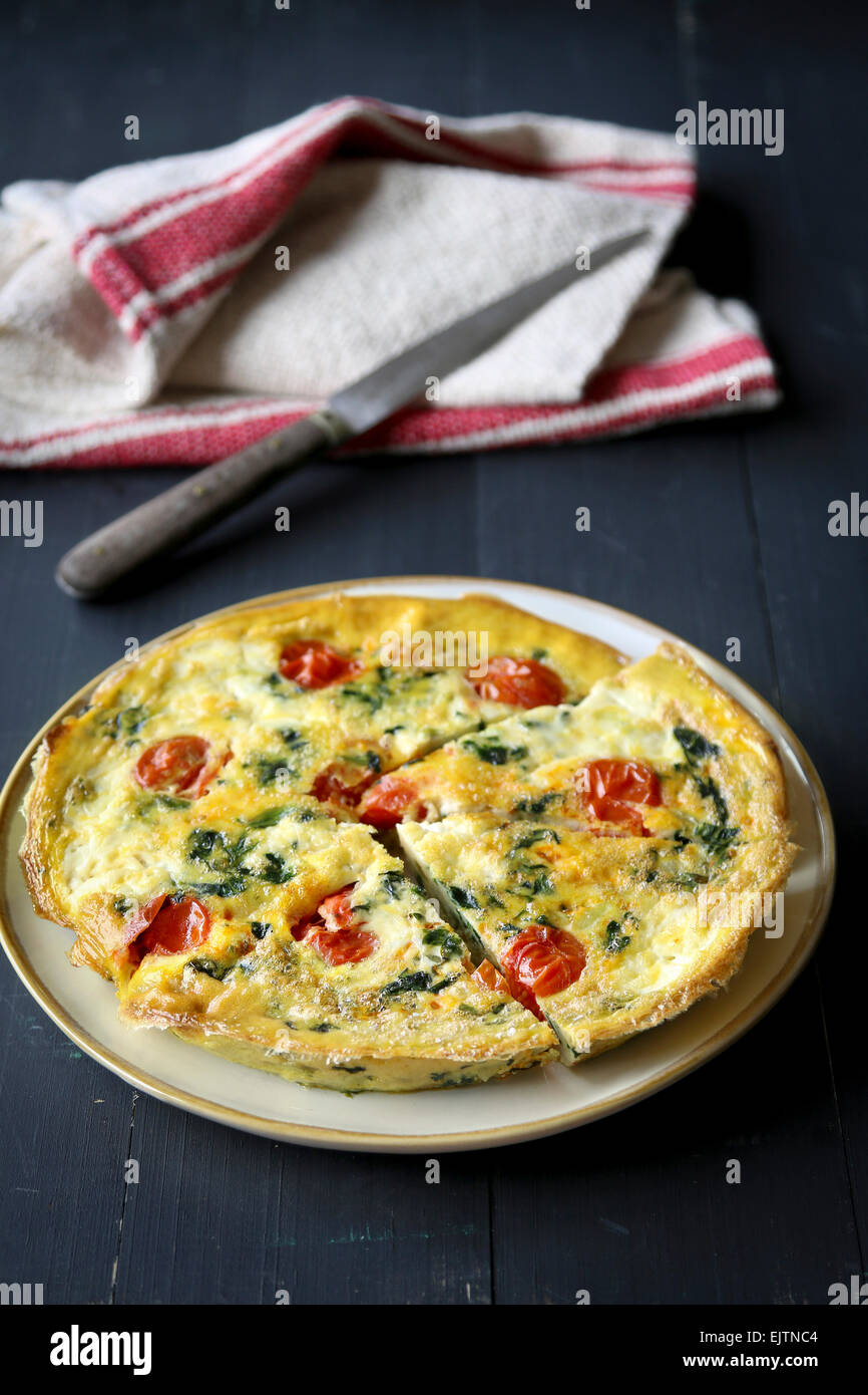 Frittata with spinach and cherry tomatoes - Stock Image
