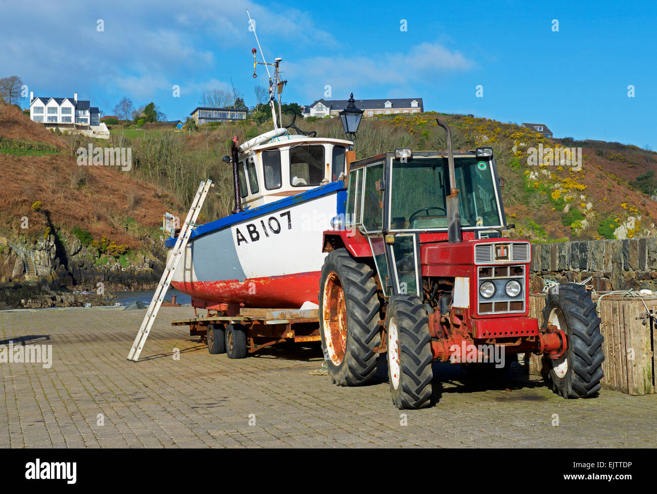 Fishing boat on trailer attached to tractor, the habour at Lower Fishguard, Pembrokeshiire, Wales UK - Stock Image