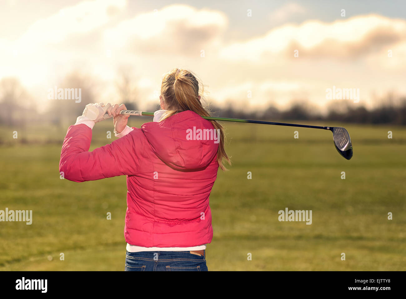 Female golfer watching her drive from the tee  after making a stroke staring down the fairway - Stock Image