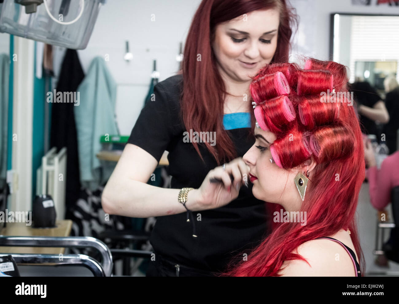 Woman hairdressing for a costume and making up a model for a fashion showcase. - Stock Image