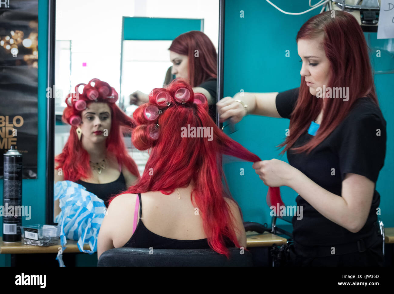 Female model having her bright red hair done by a hairdresser in a beauty salon for a fashion showcase. - Stock Image