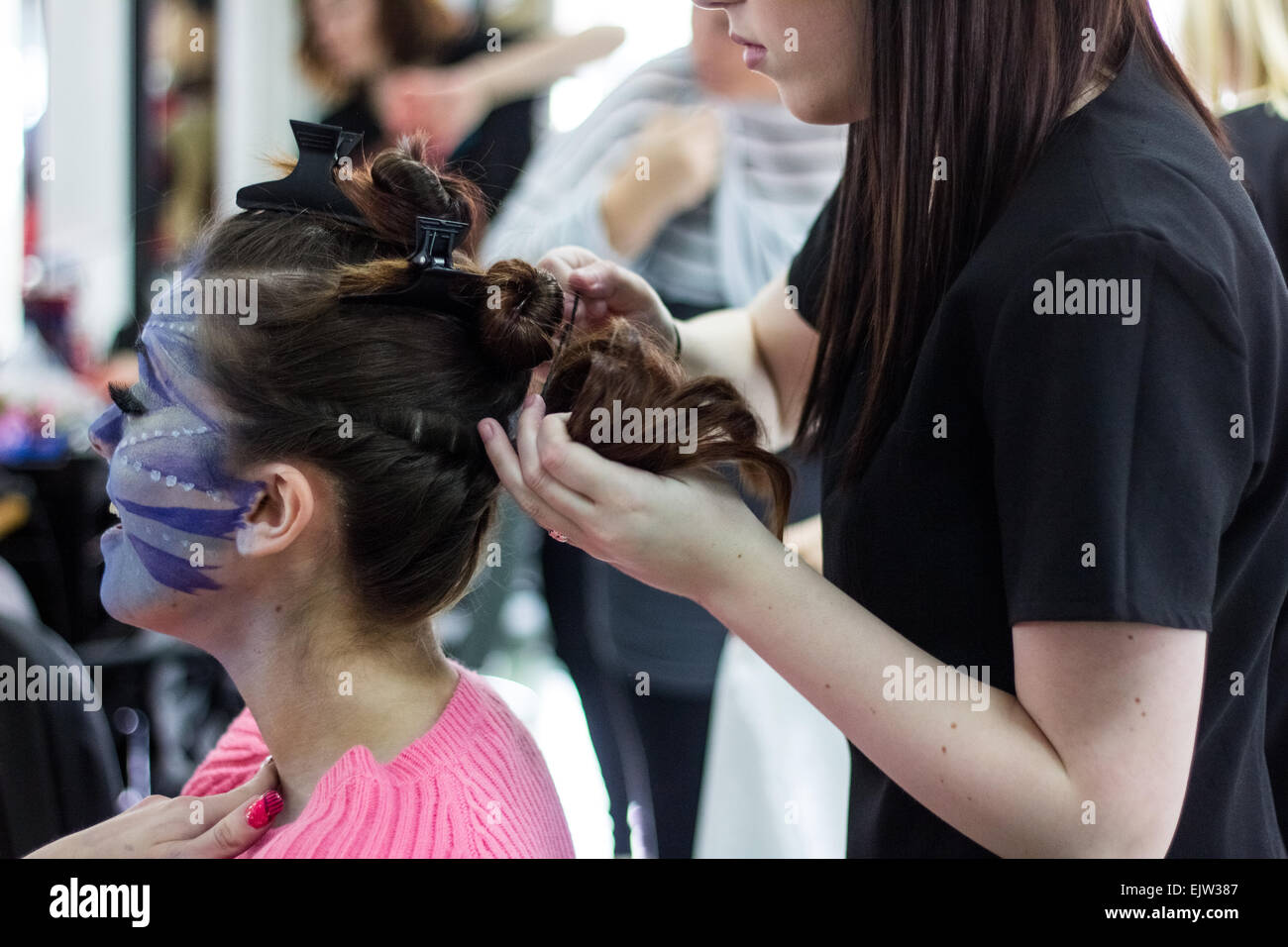Female hairdresser in a salon styling a female models hair for a costume in a theatre fashion show. - Stock Image