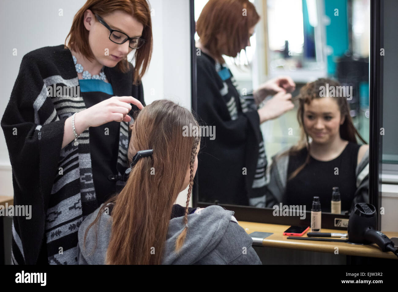 Female hairdresser in glasses braiding a model's hair for a fashion showcase both in the reflection of a mirror - Stock Image