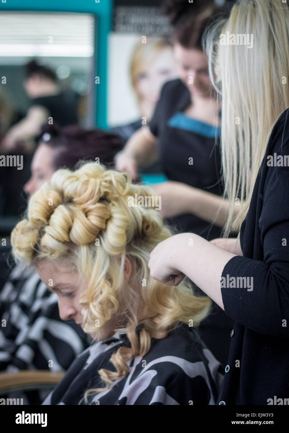 Hairdressers styling two female models in a hair salon for a fashion show,with the one in the foreground having Stock Photo