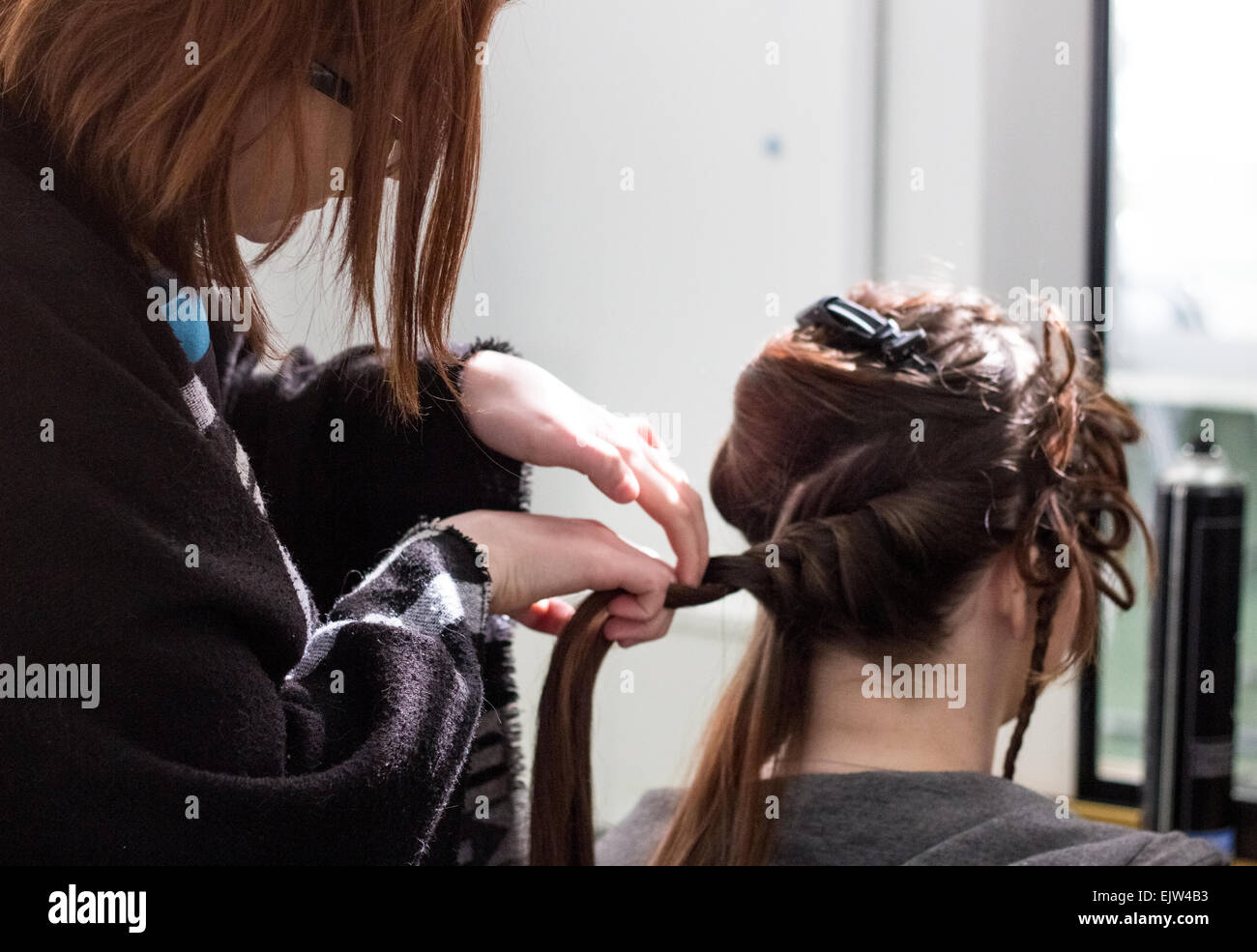 Female hairdresser twisting and braiding a female models hair ready for a fashion showcase. - Stock Image