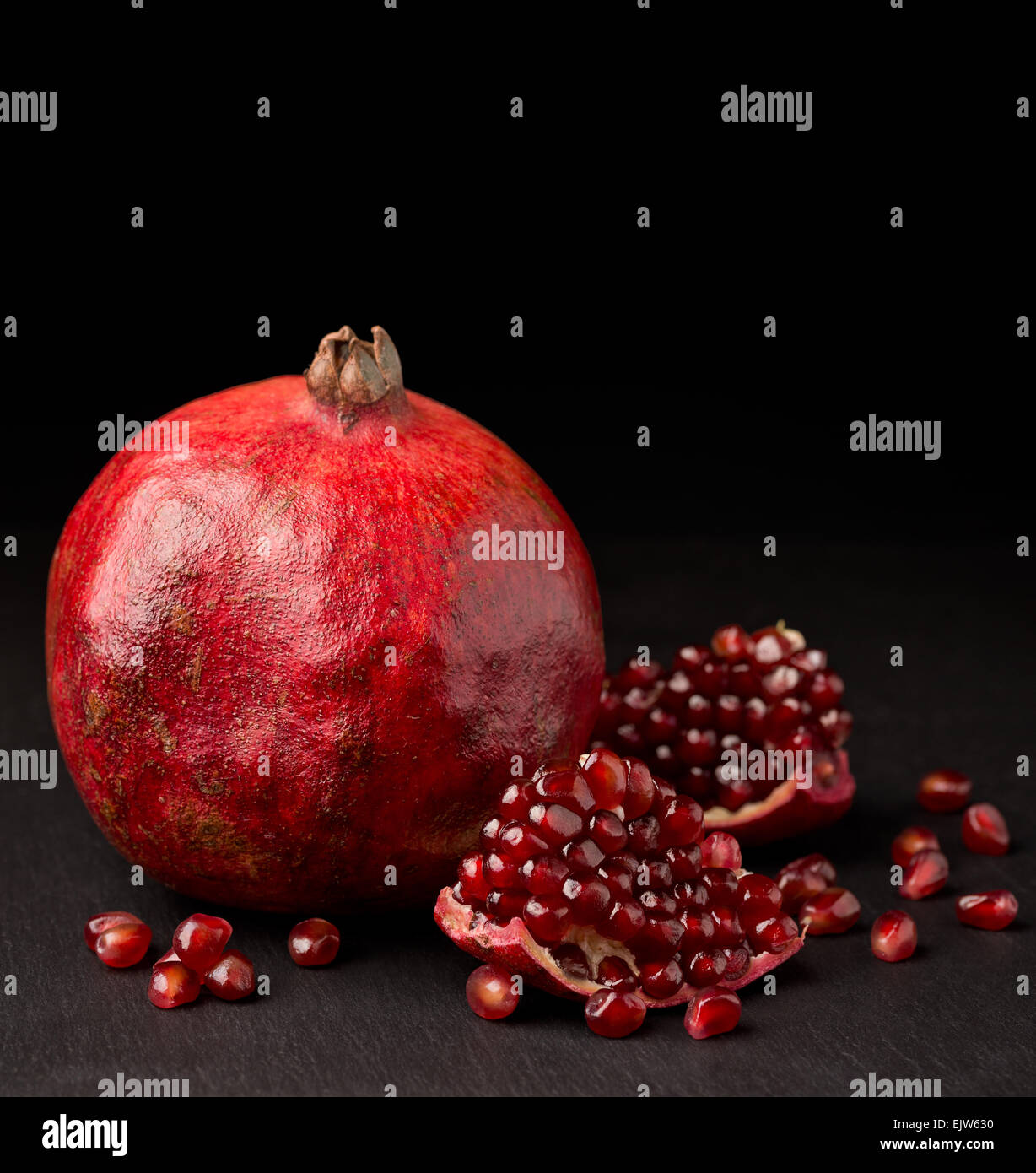 pomegranate with pieces on dark background - Stock Image