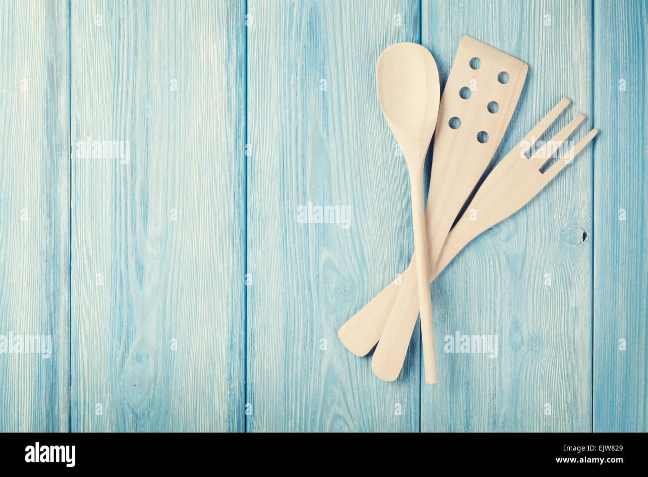 Kitchen cooking utensils over wooden table background. Top view with ...