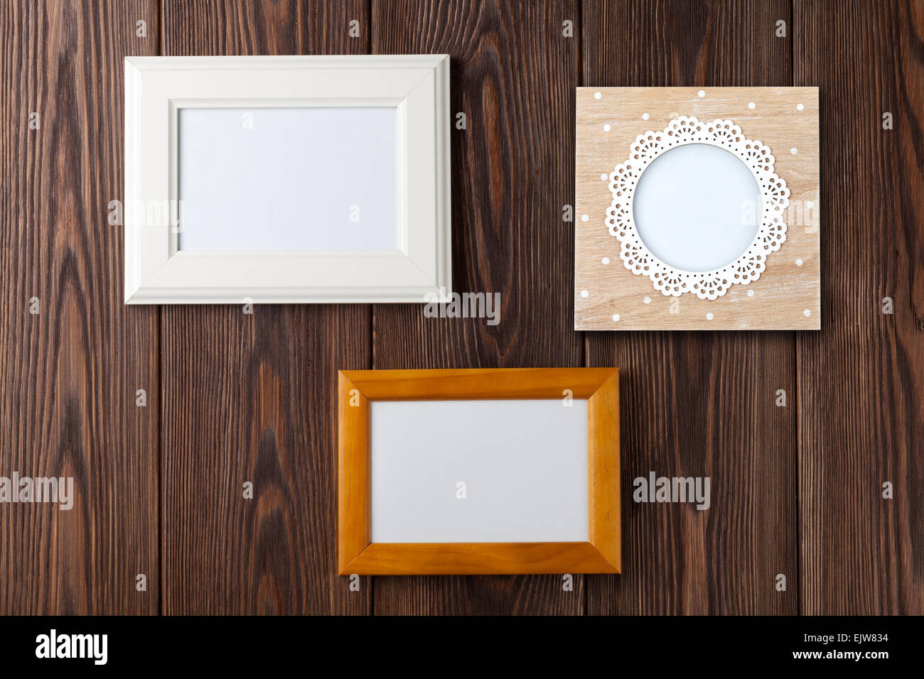 Photo frames on wooden wall with copy space - Stock Image